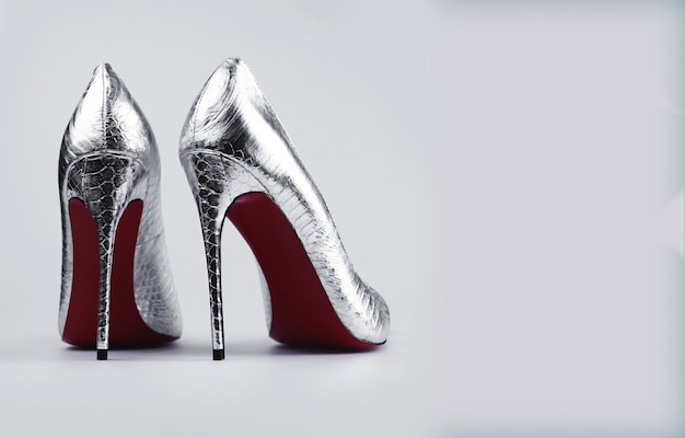Stylish female silver shoes over grey