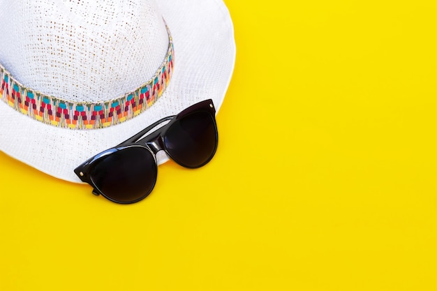Стильная женская соломенно-белая шляпа с разноцветным узором и модные черные солнцезащитные очки изолированы на ярко-желтой стене