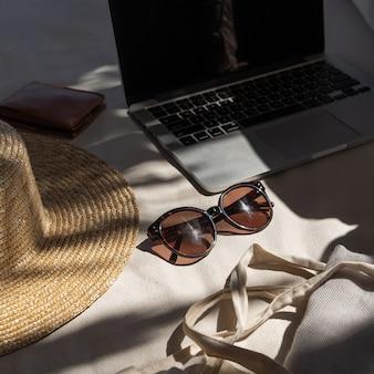 세련된 여성 선글라스, 밀짚 모자, 쇼핑 가방, 베개가 달린 흰색 라운지 소파에 노트북.