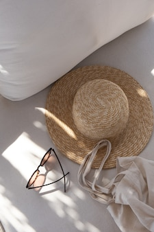Stylish female sunglasses, straw hat, shopper bag on white lounge couch with pillows