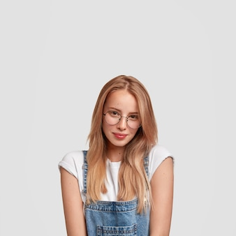 Stylish female teenager wears spectacles and denim dungarees, looks positively directly