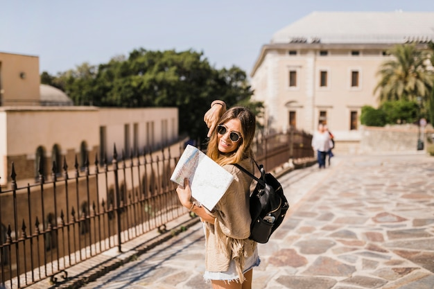Stylish female tourist pointing finger at map
