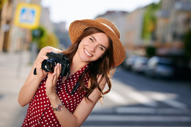 Stylish female traveler spending holiday trip on hobby taking photos of urban standing on street woman photographer