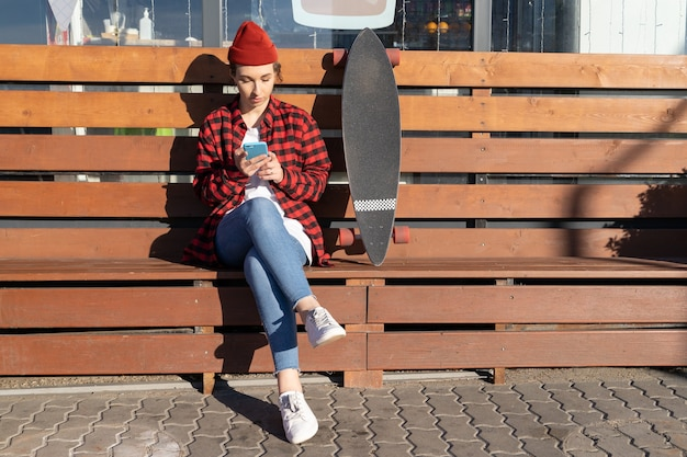 Stylish female in trendy red hat use smartphone chat outdoors send message sit next to longboard