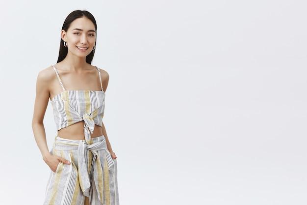 白い壁に生意気に見えるスタイリッシュなフェミニンな若いアジアの女性