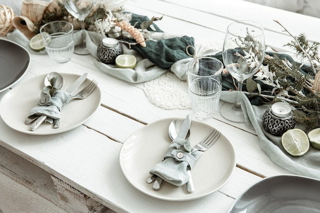 木製の表面にスカンジナビアの装飾の詳細を備えたスタイリッシュなお祝いのテーブルセッティング。