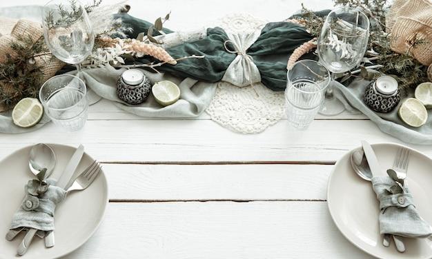Elegante tavola festiva con dettagli di arredamento scandinavo su una superficie di legno.