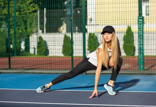 테니스 코트에서 운동하기 전에 스트레칭을 하는 세련된 금발 여성, 야외 촬영