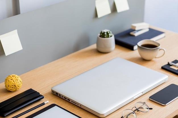ノートパソコン、タブレット、モバイル画面、サボテン、一杯のコーヒー、メモ、モダンなコンセプトの事務用品を備えた木製の机の上にスタイリッシュなフラットレイビジネス構成。