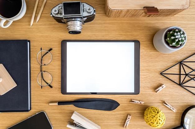 ホームオフィスのモダンなコンセプトのモックアップタブレット、サボテン、メモ、写真カメラ、事務用品を備えた木製の机の上にスタイリッシュなフラットレイビジネス構成。