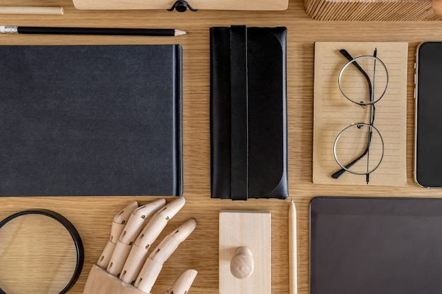 Stylish flat lay business composition on the wooden desk in modern concept of home office