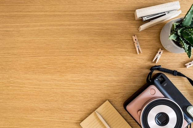 Stylish flat lay business composition on the wooden desk with photo camera, cacti, pen, copy space and office supplies in modern concept.