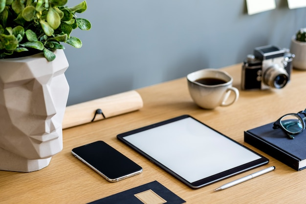 Stylish flat lay business composition on the wooden desk with  tablet, cacti, notes, photo camera and office supplies in modern concept of home office.