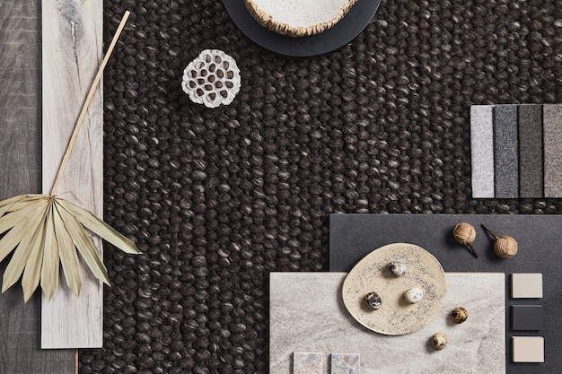 Stylish flat lay composition of architect moodboard with samples of building, brown textile and natural materials and personal accessories. top view, template.