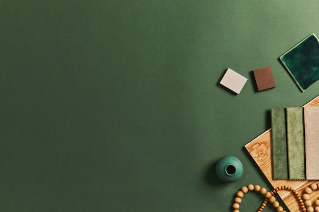 Stylish flat lay composition of creative architect moodboard design with samples of building, textile and natural materials and personal accessories. top view, green background, template.