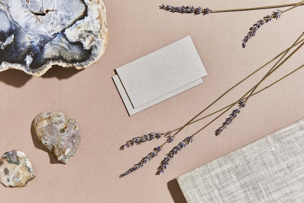 모의 방문 카드, 직물, 암석, 나무, 천연 재료, 마른 식물 및 개인 액세서리를 사용한 독창적인 인테리어의 세련된 평면 구성. 중간 색상, 상위 뷰, 템플릿입니다.