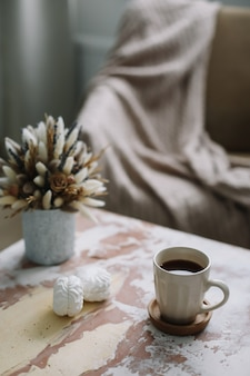 Стильная квартира с чашкой кофе с зефиром и цветами