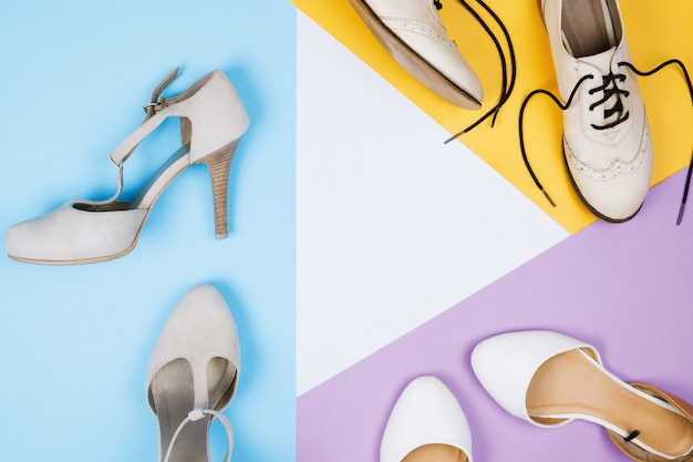 Stylish flatlay with various female fashionable footwear: brogues, flats, high heeled shoes on blue, violet, white and yellow background. copyspace