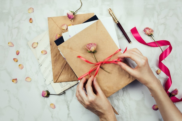 Stylish flatlay with woman's hands tying  the bow on vintage envelopes with letters or invitations on marble background