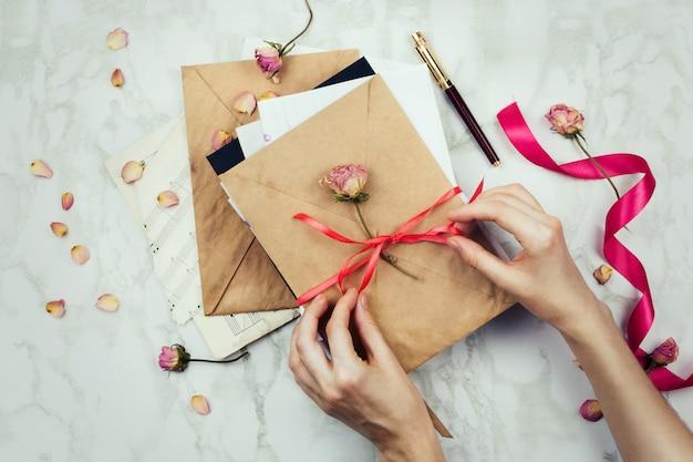文字または大理石の背景に招待状のビンテージ封筒に弓を結ぶ女性の手でスタイリッシュなフラットレイ