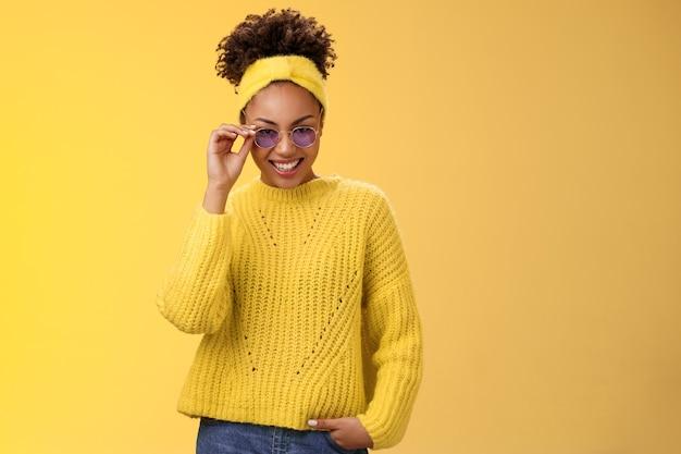 Стильная кокетливая современная афро-американская женщина с афро-прической в свитере с повязкой на голову трогает солнцезащитные очки ...
