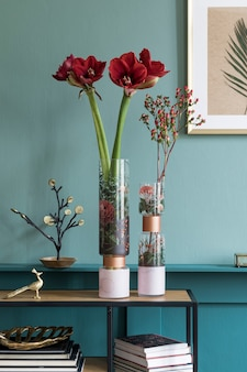 Stylish and floral composition of beautiful flowers in modern vase on the bookstand with elegant accessories and furnitures. blossom concept at living room. green walls. interior design.
