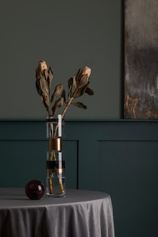 Stylish and floral composition of beautiful flowers in modern vase on the design table with elegant accessories. minimalistic. blossom concept at living room. green walls. interior design..
