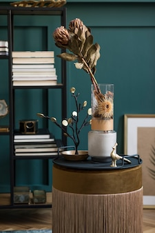 Stylish and floral composition of beautiful flowers in modern vase on the velvet pouf with elegant accessories and furnitures. blossom concept at living room. green walls. interior design.