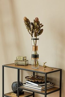 Stylish and floral composition of beautiful flowers in modern vases on the design shelf with elegant accessories. blossom concept with shadows on the beige wall. interior design.