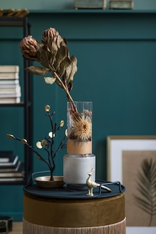 Stylish and floral composition of beautiful flowers in modern vases on the design shelf with elegant accessories. blossom concept with shadows on the beige wall. interior design..