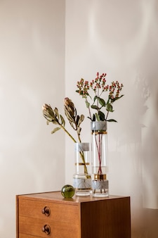 Stylish and floral composition of beautiful flowers in modern vases on the retro wooden commode with elegant accessories. blossom concept with shadows on the beige wall. interior design..