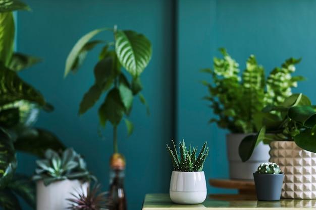 아름다운 식물, 선인장, 다육식물이 있는 세련된 꽃 구성과 대리석 커피 테이블에 있는 힙스터 냄비. 내츄럴한 거실. 녹색 벽입니다. 가정 원예 개념입니다. 주형. 프리미엄 사진