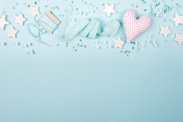 Stylish frame border with cute decoration: heart, lace ribbon, stars and sequins with copy space for text on blue background. flat lay, top view