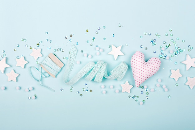 Stylish frame border with cute decoration: heart, lace ribbon, stars and sequins with copy space for text on mint background. flat lay, top view