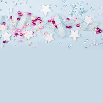 Стильная рамка с милым украшением: кружевная лента, звезды, блестки и розовые жемчужные бусины с копией пространства для текста на синем фоне. плоская планировка, вид сверху. детские концепции.