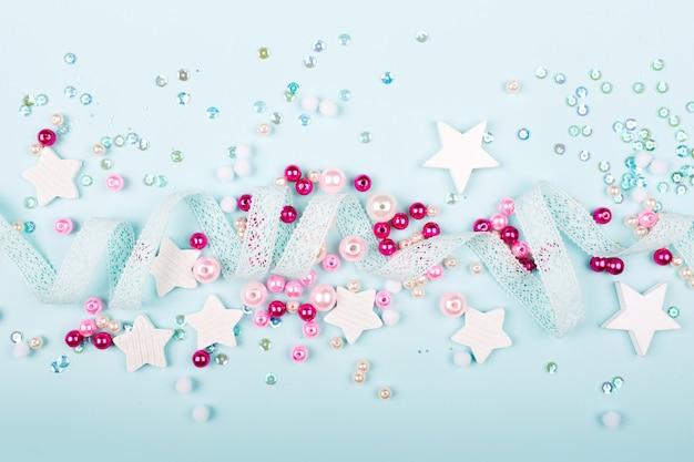 Стильная рамка с милым украшением: кружевная лента, звезды, блестки и розовые жемчужные бусины с копией пространства для текста на синем фоне. плоская планировка, вид сверху