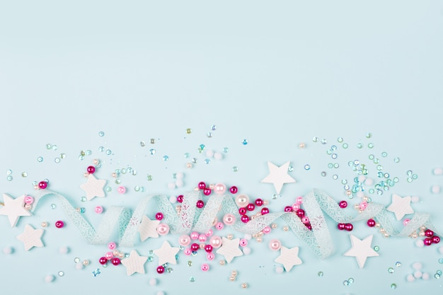 Stylish frame border with cute decoration:  lace ribbon, stars, sequins and pink pearl beads  with copy space for text on blue background. flat lay, top view. baby concept.