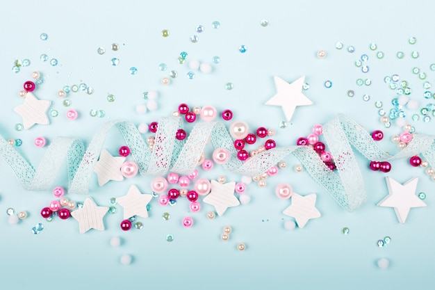 Stylish frame border with cute decoration:  lace ribbon, stars, sequins and pink pearl beads  with copy space for text on blue background. flat lay, top view
