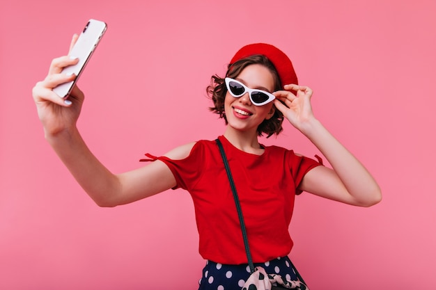 Stylish french girl with tattooes making selfie. elegant white woman in beret and sunglasses taking picture of herself.