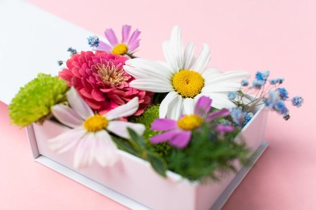 Стильная композиция из свежих цветов в белой подарочной коробке на розовом фоне