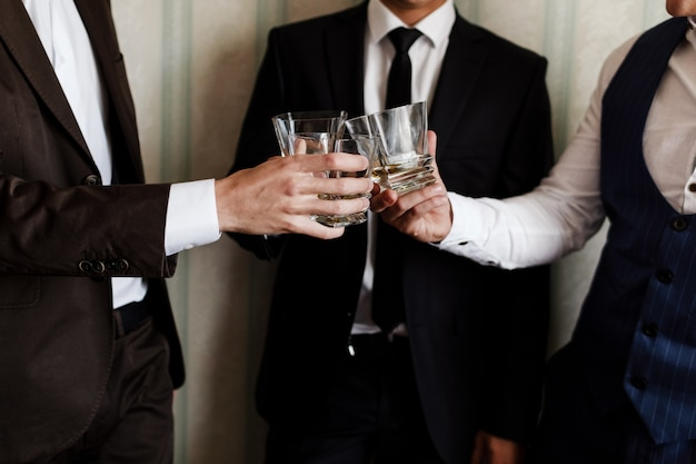 Stylish friends businessmen in suits toasting with glasses of whiskey indoors, closeup. groom's morning