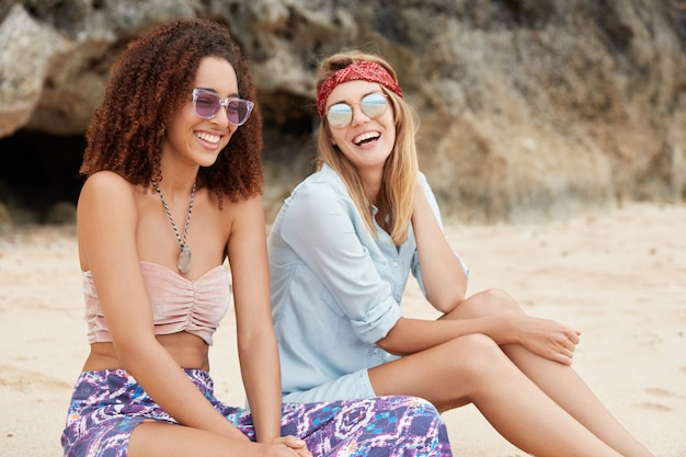 Stylish friends sitting on the beach