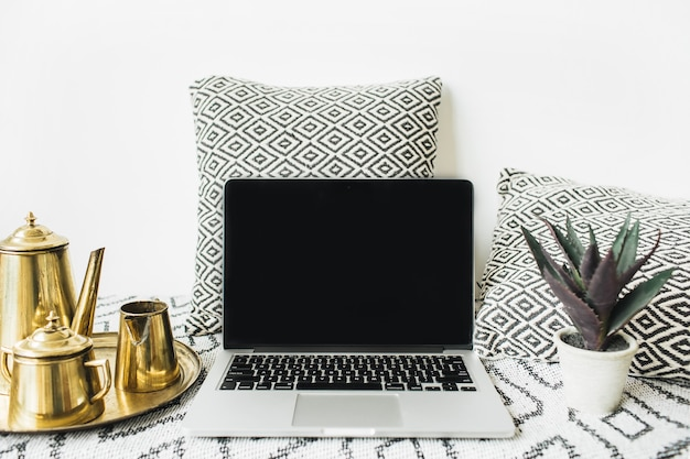 Stylish front view home office desk workspace with blank screen laptop, golden teapot on tray and succulent