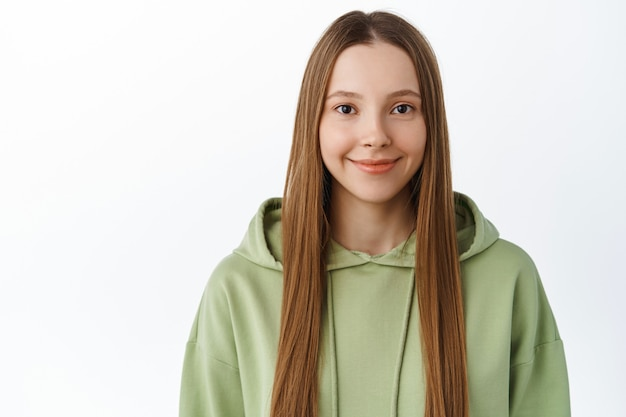 Stylish gen-z girl with long natural hair and nude makeup, wearing green hoodie, smiling cute and happy at front, standing over white wall