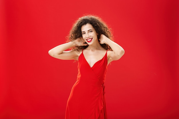 Stylish gentle caucasian girl with curly hairstyle and evening makeup touching strands of hair check...