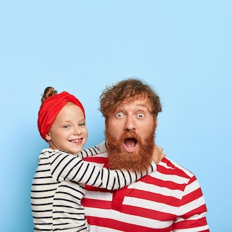 Stylish ginger daughter and father posing together