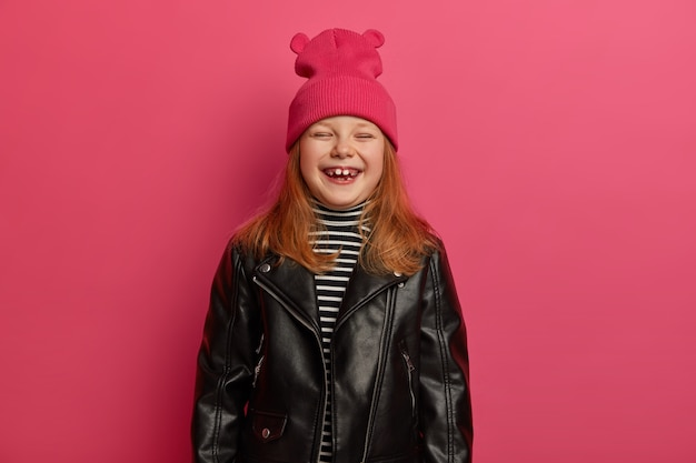 Elegante ragazza adorabile zenzero ride sinceramente, chiude gli occhi, si sente molto felice, si rallegra della bella giornata, trascorre il tempo libero con madre e padre, indossa cappello rosa e giacca di pelle, si prepara per la scuola