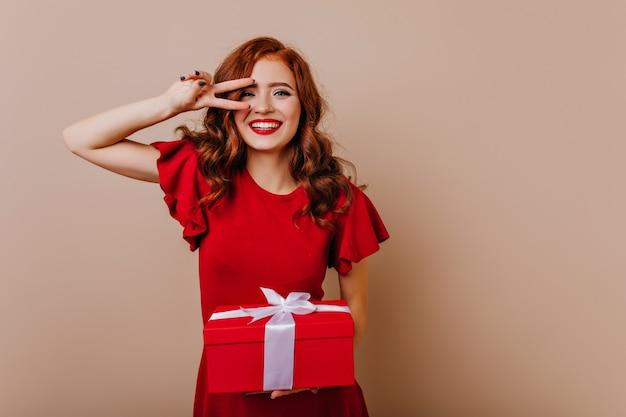 크리스마스를 위해 준비하는 세련 된 생강 여자. 새 해 파티를 즐기는 빨간 드레스에 행복 백인 여자의 실내 사진.