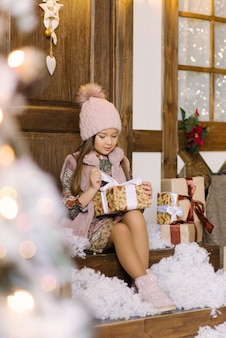 Stylish girl in a beret holds a christmas gift and opens it, sitting on the porch of a snow-covered house