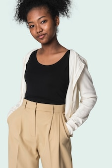 Ragazza alla moda in maglietta nera con cardigan beige e servizio di moda giovanile dei pantaloni